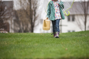 Low section of girl carrying watering can and umbrella while walking on grassy field - CAVF26414