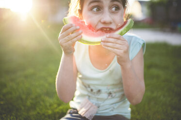 Girl eating watermelon while sitting on grassy field - CAVF26417