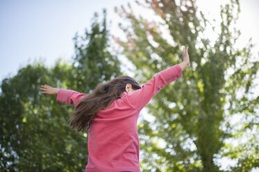 Low angle view of playful girl with arms outstretched by trees in garden - CAVF26423