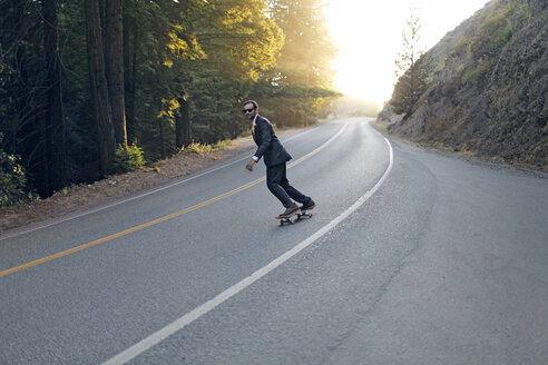 Businessman skateboarding at street on sunny day - CAVF26543