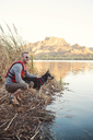 Side view of smiling man crouching with dog at lakeshore - CAVF26651