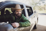 Happy man sitting in pick-up truck on road - CAVF26654