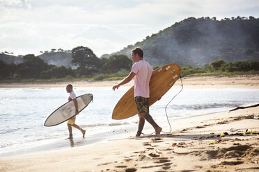 Side view of male surfers carrying surfboards while walking on beach - CAVF26734