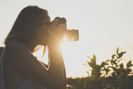 Side view of woman photographing through old-fashioned camera against sky during sunset - CAVF26740