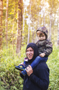 Portrait of happy father carrying son on shoulders in forest - CAVF26749