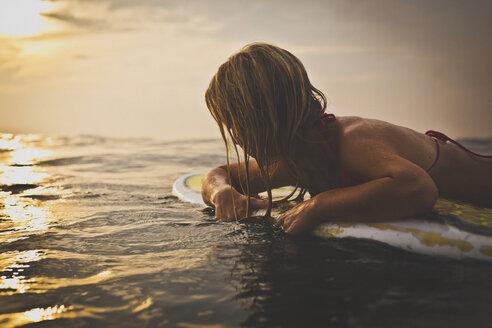 Woman lying on surfboard in sea against sky - CAVF26770