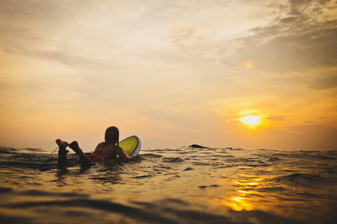 Woman lying on surfboard in sea during sunset - CAVF26773