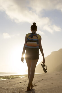 Rear view of woman with backpack holding sandals while walking at beach against cloudy sky - CAVF26866