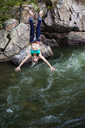 Woman hanging on rope while slacklining over river - CAVF26878