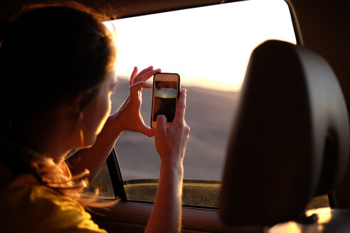 Woman in car photographing sky during sunset - CAVF26881