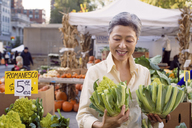 Happy mature woman inspecting romanesco broccolis at farmer's market - CAVF26890