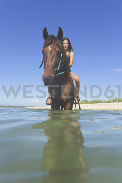Indonesia, Bali, Woman sitting on horse, in water - KNTF01104