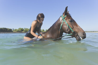 Indonesia, Bali, Woman sitting on horse in water - KNTF01110