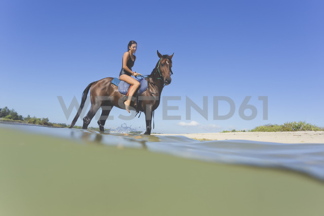 Indonesia, Bali, Woman sitting on horse - KNTF01113