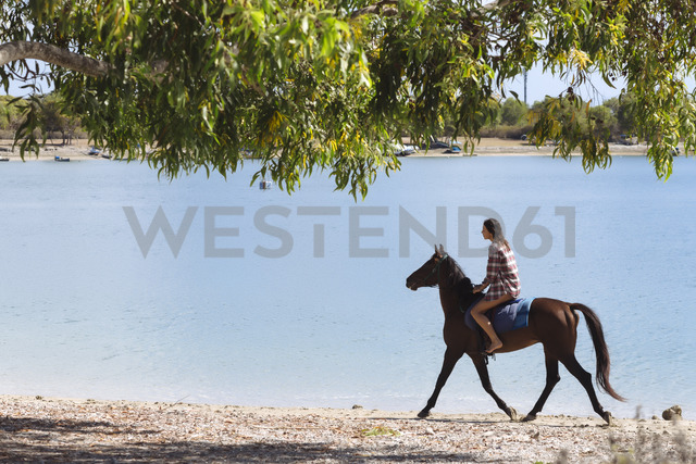 Indonesia, Bali, Woman riding a horse at beach - KNTF01116