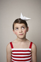 Portrait of little girl with paper boat on her head - FSF00998