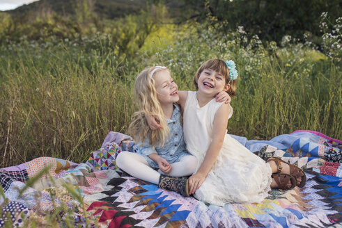Cheerful sisters sitting on blanket in park - CAVF26943