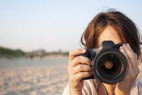 Close-up of woman holding camera - CAVF27057