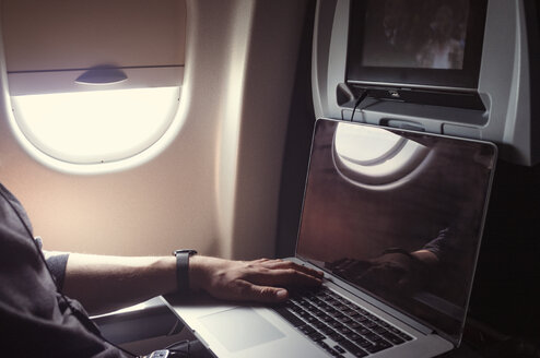 Cropped image of male passenger using laptop in airplane - CAVF27075