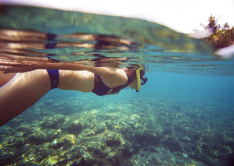 Side view of woman snorkeling in sea on sunny day - CAVF27093