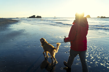 Hiker with Golden Retriever walking at Ruby beach against sky during sunset - CAVF27114
