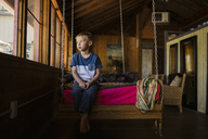 Thoughtful boy sitting on swing at home - CAVF27165