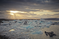 Iceland, South of Iceland, Joekulsarlon glacier lake, icebergs and sunshine through clouds - STCF00531