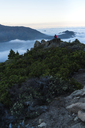 Distant view of woman sitting on top of mountain by cloudscape - CAVF27290