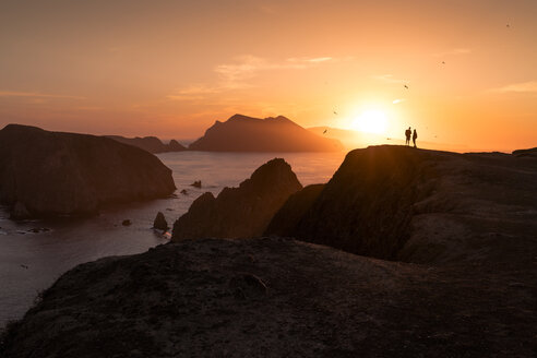 Silhouette couple standing on rock formation by sea against sky - CAVF27308
