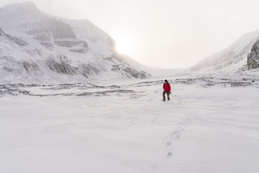 Hiker walking on snow covered landscape during foggy weather - CAVF27335