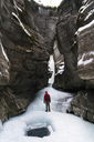 Rear view of hiker with backpack standing on frozen stream amidst mountains - CAVF27341
