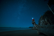 Hiker wearing headlamp sitting on tree trunk at La Push beach against star field - CAVF27347
