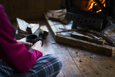 Midsection of man having drink while sitting by wood burning stove in cottage - CAVF27353