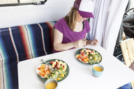 High angle view of happy woman having food while sitting in travel trailer - CAVF27383