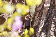 High angle view of female hiker looking away while standing by rock formation during sunny day - CAVF27389