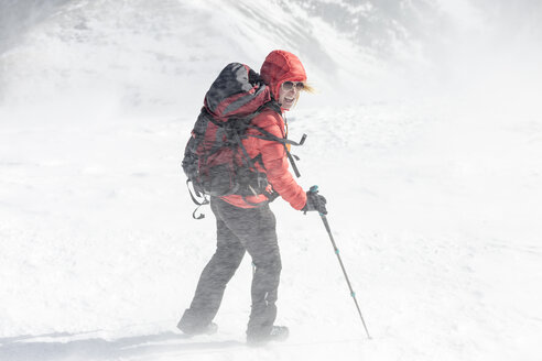 High angle view of female hiker with backpack holding hiking poles during snowstorm - CAVF27398