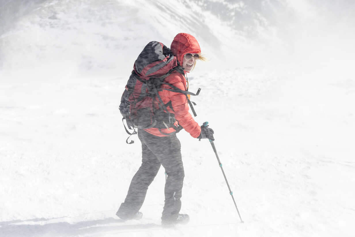 High angle view of female hiker with backpack holding hiking poles during snowstorm - CAVF27398 - Cavan Images/Westend61