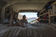 Woman looking at view while lying in camper trailer - CAVF27407