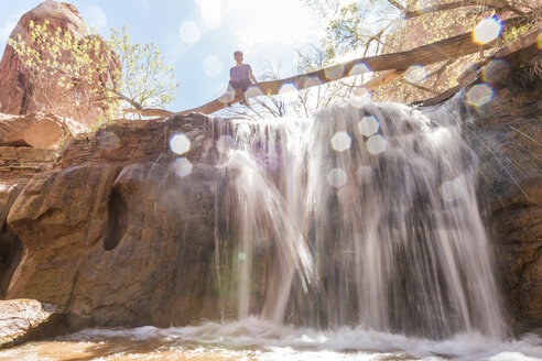 Low angle view of woman sitting on tree trunk over waterfall during sunny day - CAVF27413