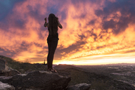Full length of carefree woman standing on rock against dramatic sky at South Mountain Park - CAVF27422