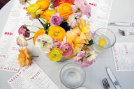 High angle view of flower vase with menus and water glasses on restaurant table - CAVF27431