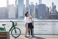 Couple taking selfie on mobile phone while standing by bicycles against cityscape - CAVF27458