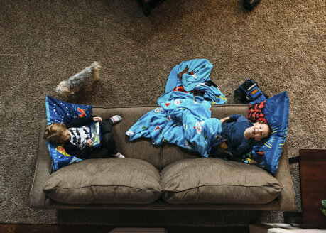Overhead view of boys lying on sofa at home - CAVF27488