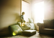 Boy standing on cushions at home - CAVF27509