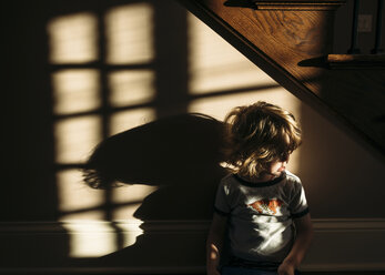 Boy sitting in beneath staircase at home - CAVF27512