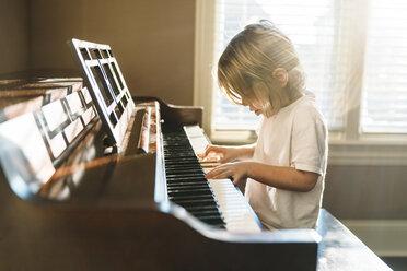 Boy practicing piano at home - CAVF27515