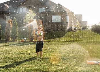 Boy squirting through water gun at backyard - CAVF27518