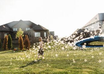 Shirtless boy playing at backyard on sunny day - CAVF27524