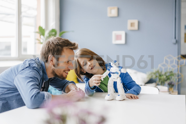 Happy father and son playing with robot on table at home - KNSF03583