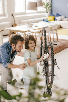 Father and son repairing bicycle together at home - KNSF03586